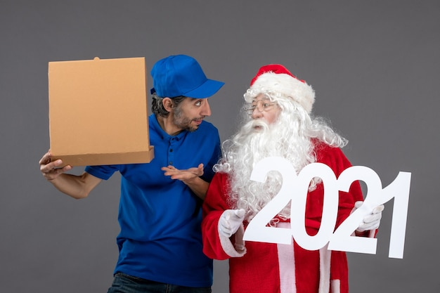 Front view of santa claus with male courier holding food box and on the grey wall