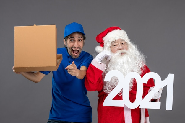 Front view of santa claus with male courier holding food box and writing on a grey wall