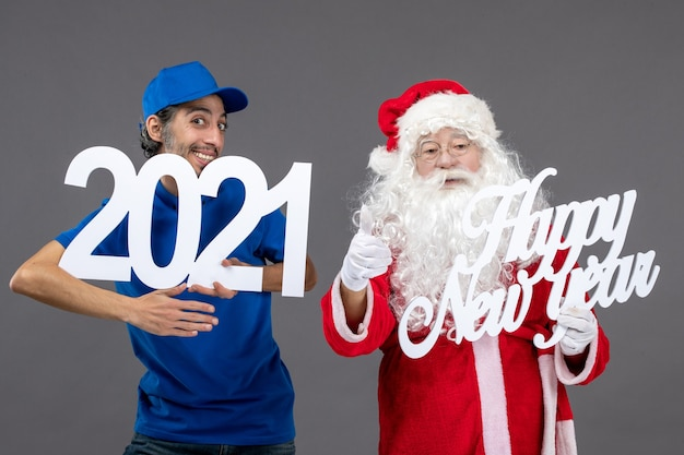 Front view of santa claus with male courier holding and happy new year and 2021 boards on a grey wall