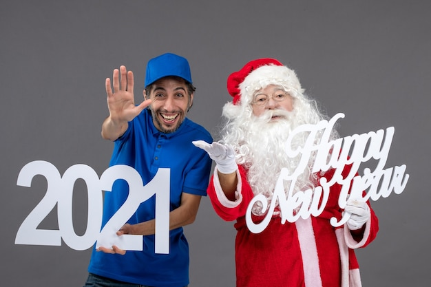 Front view of santa claus with male courier holding and happy new year and 2021 boards on grey wall