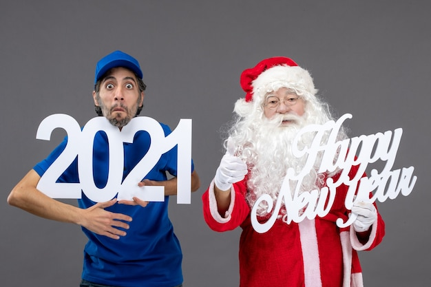 Front view of santa claus with male courier holding and happy new year and 2021 boards on the grey wall