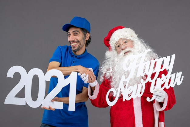 Front view of santa claus with male courier holding happy new year and 2021 boards on the grey wall