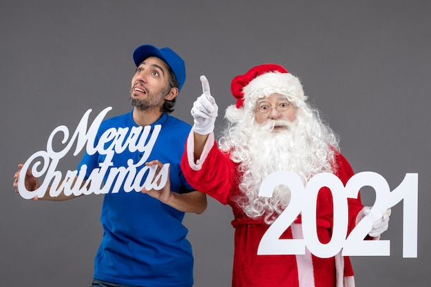 Front view of santa claus with male courier holding merry christmas and 2021 banner on a grey wall