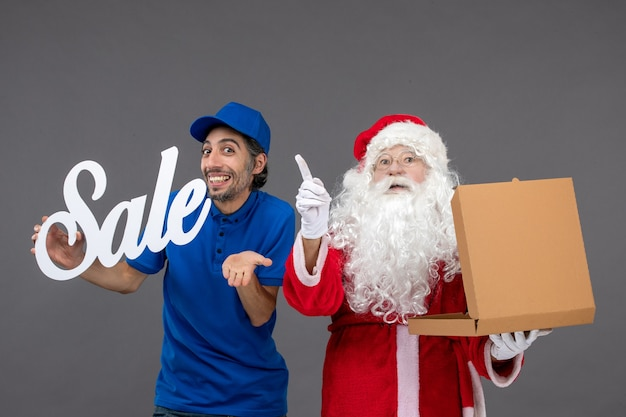Front view of santa claus with male courier holding sale banner and food box on the grey wall