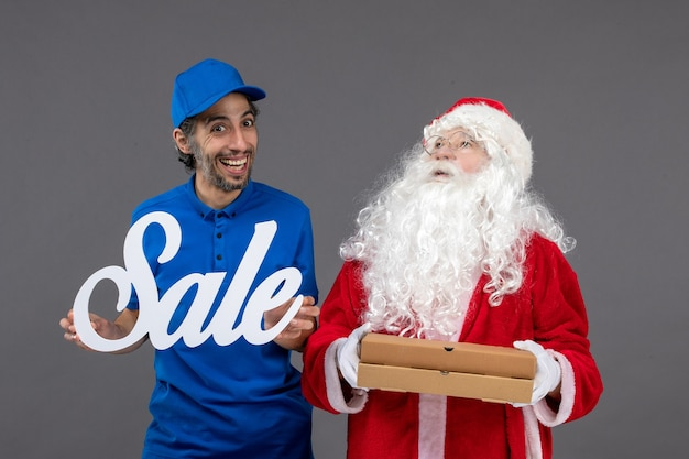 Front view of santa claus with male courier holding sale banner and food boxes on grey wall