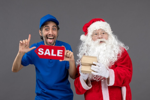 Front view of santa claus with male courier holding sale banner and food packages on grey wall