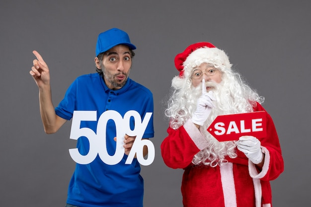 Front view of santa claus with male courier holding and sale banner on grey wall