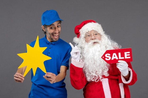 Front view of santa claus with male courier holding sale banner and yellow sign on grey wall