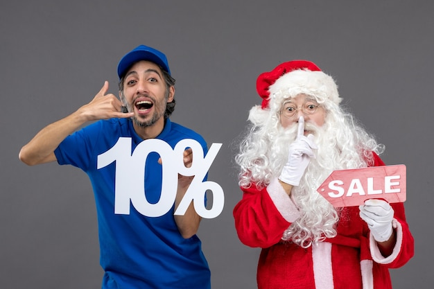 Front view of santa claus with male courier holding sale banners on grey wall