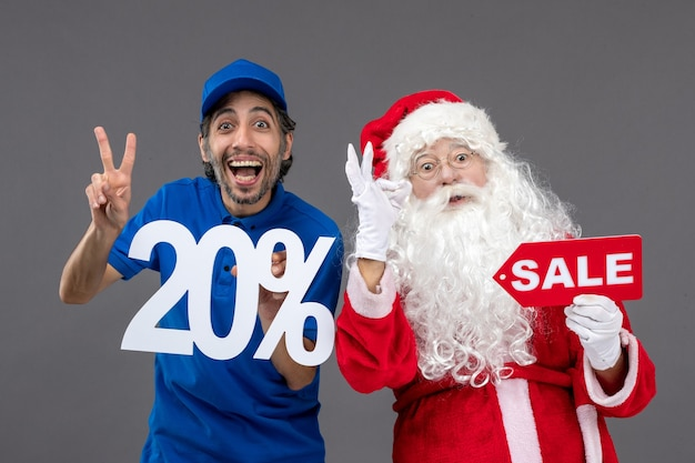 Front view of santa claus with male courier holding sale banners on a grey wall