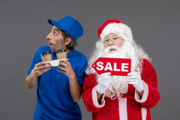 Front view of santa claus with male courier holding sale board and coffee on the grey wall