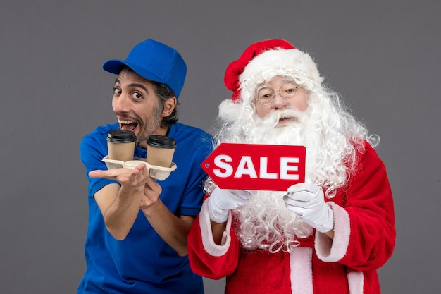 Front view of santa claus with male courier holding sale writing and coffee on a grey wall