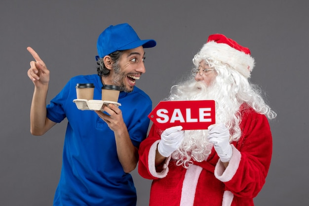 Front view of santa claus with male courier holding sale writing and coffee on grey wall