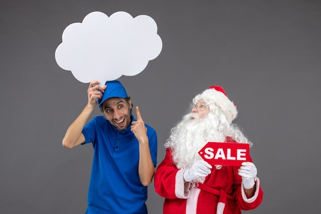Front view of santa claus with male courier holding white cloud sign and sale on grey wall