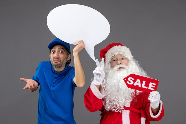 Front view of santa claus with male courier holding white sign and sale banner on grey wall