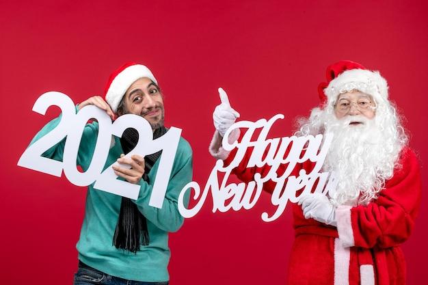 男性の抱擁と赤い新年のクリスマス休暇に幸せな新年の書き込みと正面図のサンタクロースは感情を提示します