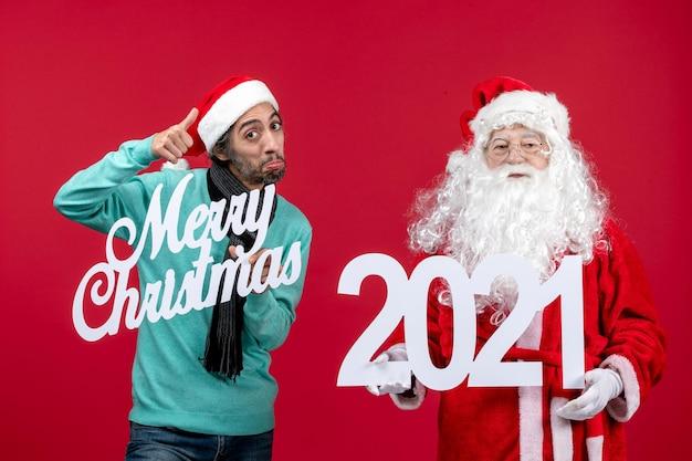男性の保持と赤いクリスマスの色のメリークリスマスの書き込みと正面のサンタクロース