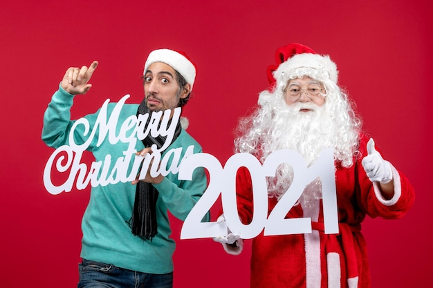 男性の保持と赤いクリスマスの感情のメリークリスマスの書き込みと正面のサンタクロース