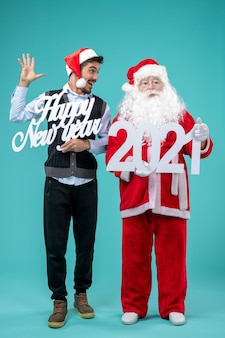 Front view of santa claus with male holding happy new year and 2021 boards on a blue wall