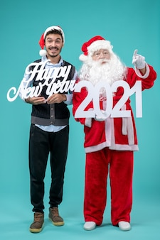 Front view of santa claus with male holding happy new year and 2021 boards on blue wall