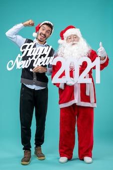 Vista frontale di babbo natale con maschio che tiene felice anno nuovo e 2021 tavole sulla parete blu