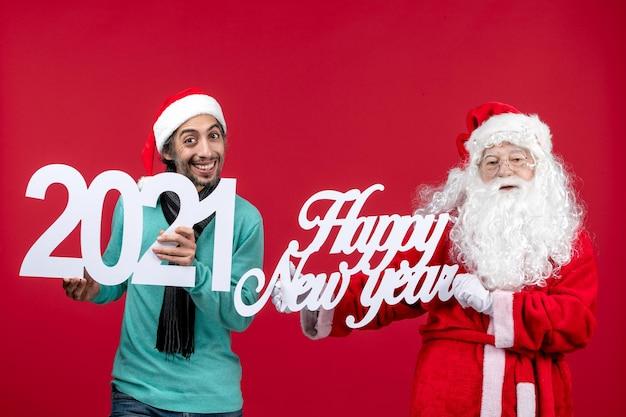 Vista frontale babbo natale con tenuta maschile e felice anno nuovo che scrive su emozione rossa capodanno