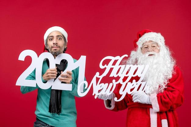 Vista frontale babbo natale con tenuta maschile e felice anno nuovo che scrive su rosso capodanno natale
