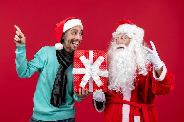 赤い贈り物の感情の赤いクリスマス新年に休日のプレゼントを保持している男性と正面のサンタクロース