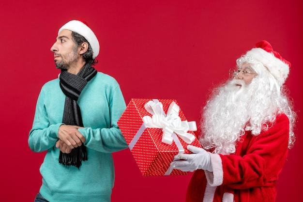 Вид спереди санта-клауса с мужчиной, держащим праздничный подарок на красном столе, красный подарок, рождественские эмоции, новый год