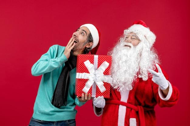 Vista frontale babbo natale con maschio che tiene regalo di festa sulla scrivania rossa regalo emozione rosso natale