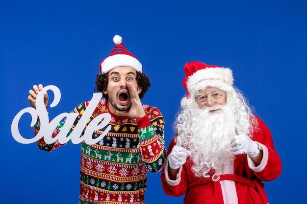 青い雪の新年のクリスマス休暇に書き込み販売を保持している男性と正面図のサンタクロース
