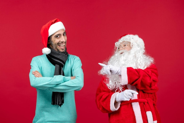 赤いクリスマス休暇の現在の感情ムードに立っているだけの男性と正面のサンタクロース