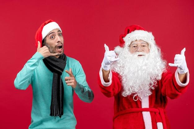 Vista frontale babbo natale con maschio in piedi sul regalo di festa di emozione di natale rosso