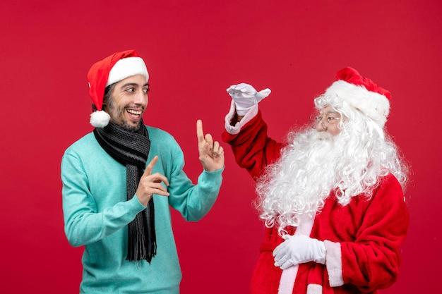 Vista frontale babbo natale con maschio in piedi sulle vacanze di emozioni natalizie presenti in rosso