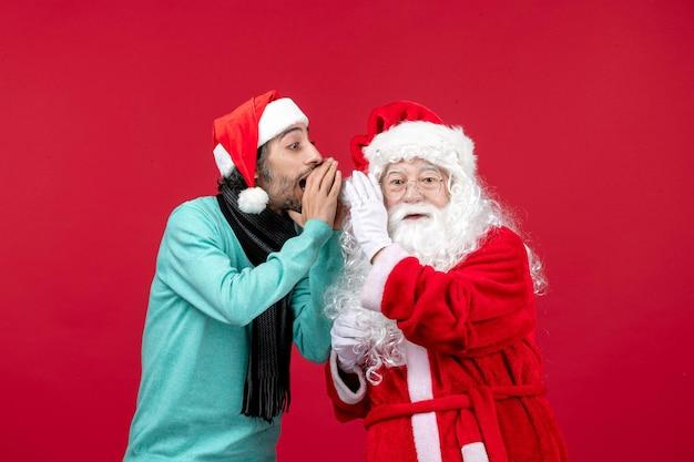 Vista frontale babbo natale con maschio in piedi su regali rossi vacanze emozione natalizia