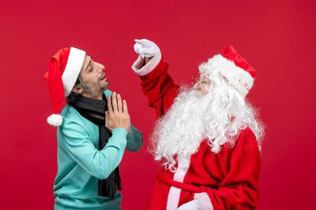 빨간색 책상에 남성이 포즈를 취하는 전면 보기 산타 클로스는 휴일 크리스마스 감정을 나타냅니다.