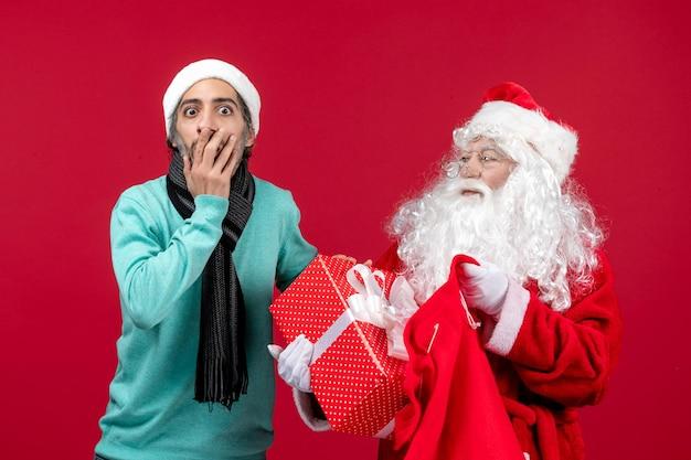 赤いクリスマスの感情の休日の色でバッグからプレゼントを取り出す男性と正面のサンタクロース