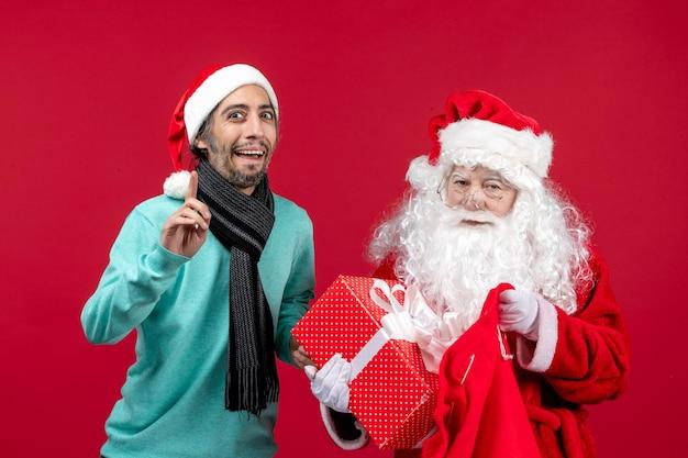 Vista frontale babbo natale con maschio che tira fuori il regalo dalla borsa sul colore rosso delle vacanze di emozione di natale