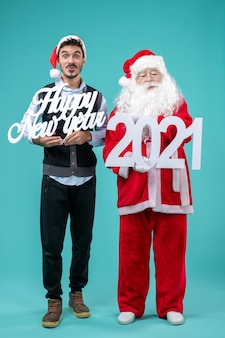 Front view of santa claus with man holding happy new year and 2021 boards on blue wall