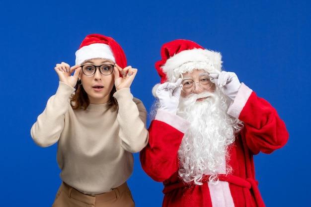 파란색 책상 색상 눈 새해 크리스마스 감정에 예쁜 여성이 서 있는 전면 보기 산타 클로스