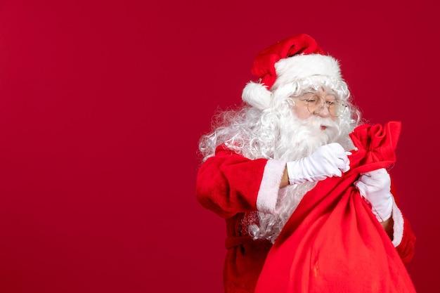 赤い新年の子供たちへのプレゼントでいっぱいの赤いバッグと正面のサンタクロース