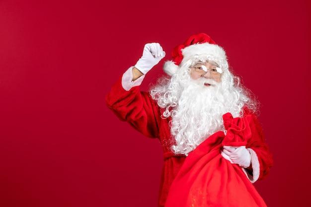 赤い新年の休日のクリスマスの感情のプレゼントでいっぱいの赤いバッグと正面のサンタクロース