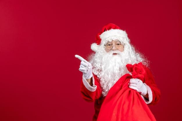 Vista frontale babbo natale con borsa rossa piena di regali sull'emozione delle vacanze di capodanno natale rosso