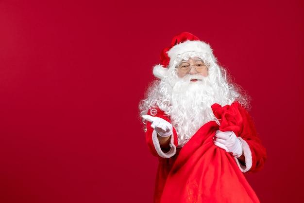 Vista frontale babbo natale con borsa rossa piena di regali sull'emozione rossa del capodanno di natale di festa
