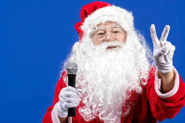 파란색 책상 색상 휴일 크리스마스 새해 눈에 마이크를 들고 빨간 양복과 흰 수염을 가진 전면 보기 산타 클로스