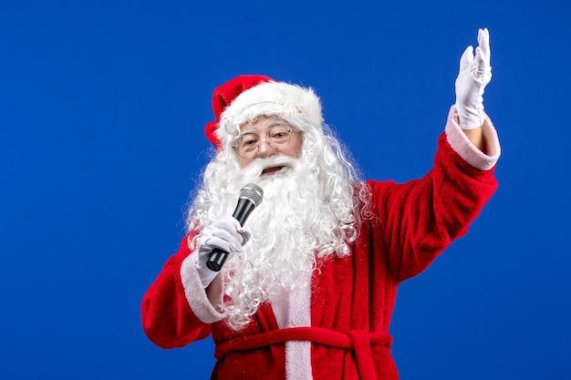 파란색 책상 색상 새해 크리스마스에 마이크를 들고 빨간 양복과 흰 수염을 가진 전면 보기 산타 클로스