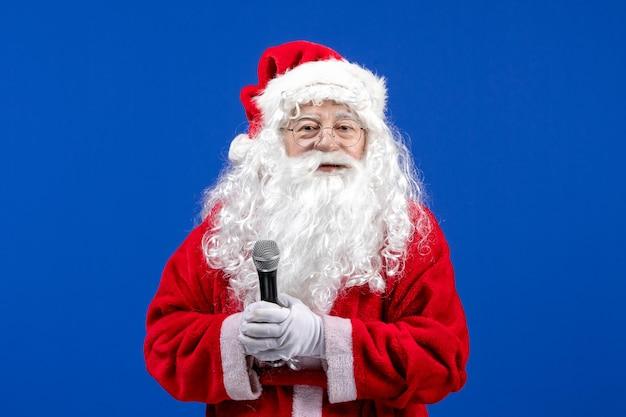 파란색 책상 색상 새해에 마이크를 들고 빨간 양복과 흰 수염을 가진 전면 보기 산타 클로스