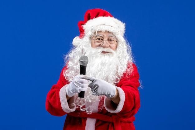 파란색 책상 눈 휴일 크리스마스 색상 새해에 마이크를 들고 빨간 양복과 흰 수염을 가진 전면 보기 산타 클로스