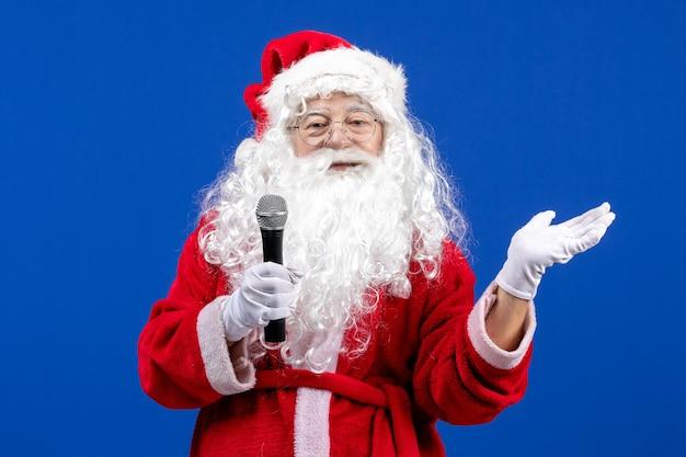 Vista frontale babbo natale con abito rosso e barba bianca che tiene il microfono durante le vacanze sulla neve blu