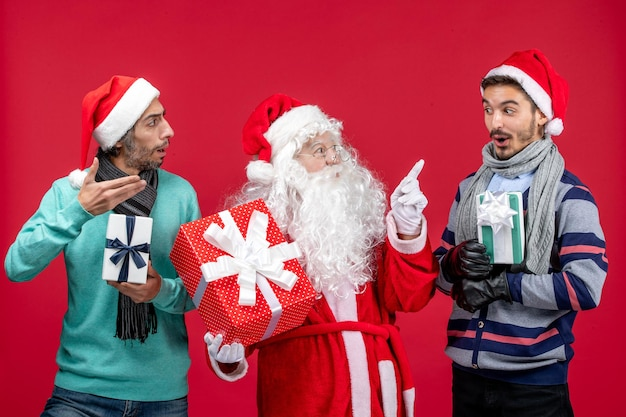 빨간색 새 해 선물 감정 크리스마스 빨간색에 선물을 들고 두 남자와 전면 보기 산타 클로스